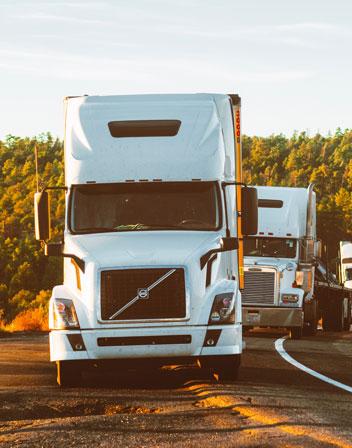 Volvo trucks standing next to road