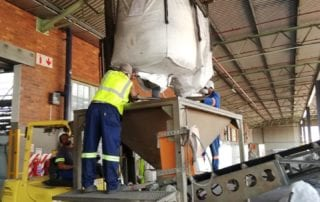 Worker emptying out silo bags for repacking