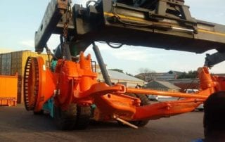 Container lifter moving heavy equipment