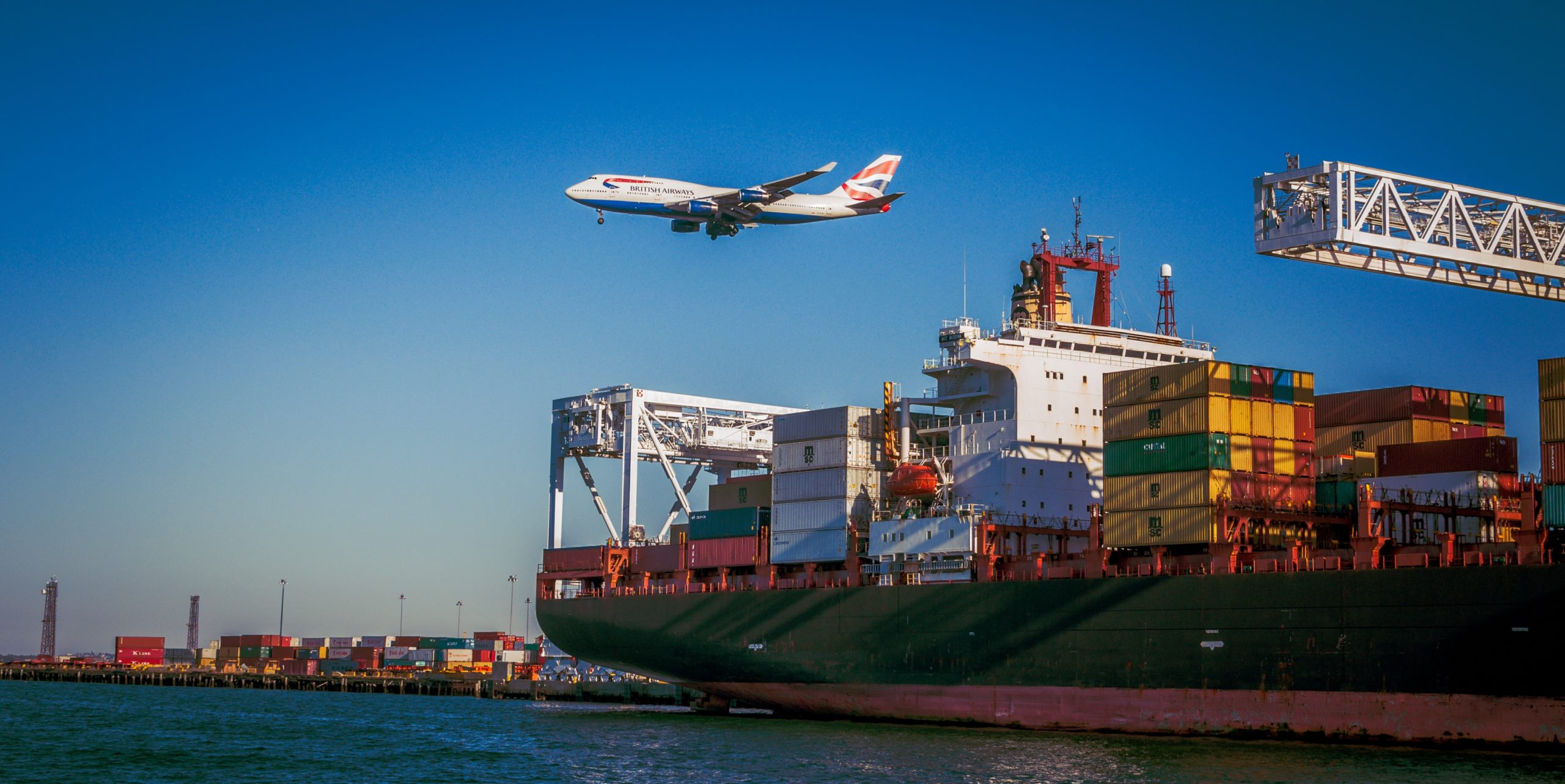Shipping container ship with low flying aeroplane