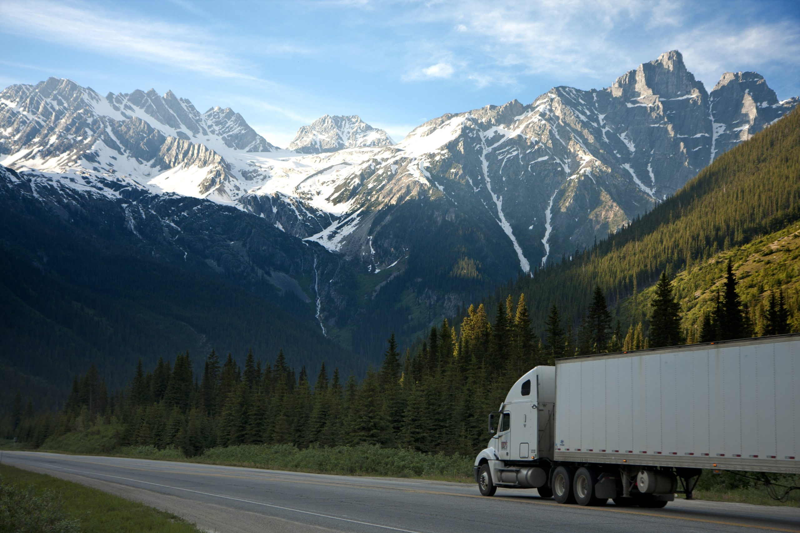 White truck driving with snow capped mountains in the background